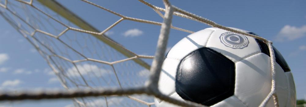 Football - soccer ball in goal against blue sky